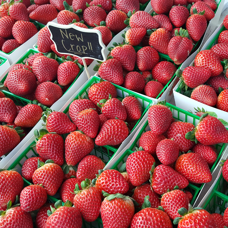 baskets of fresh strawberries at a farmers market
