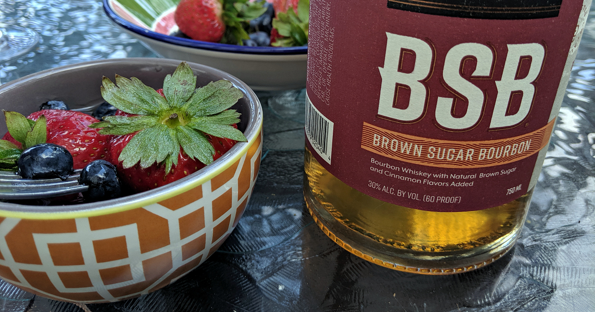 bottle of bourbon next to berries