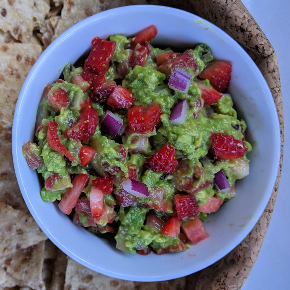 strawberry guacamole in white bowl with chips