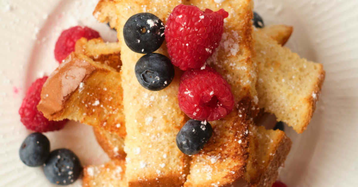 french toast sticks sprinkled with powdered sugar and topped with fresh berries.