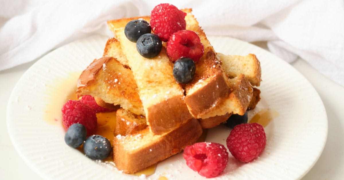 Air fryer egg-free french toast sticks topped with fresh berries served on white plate.