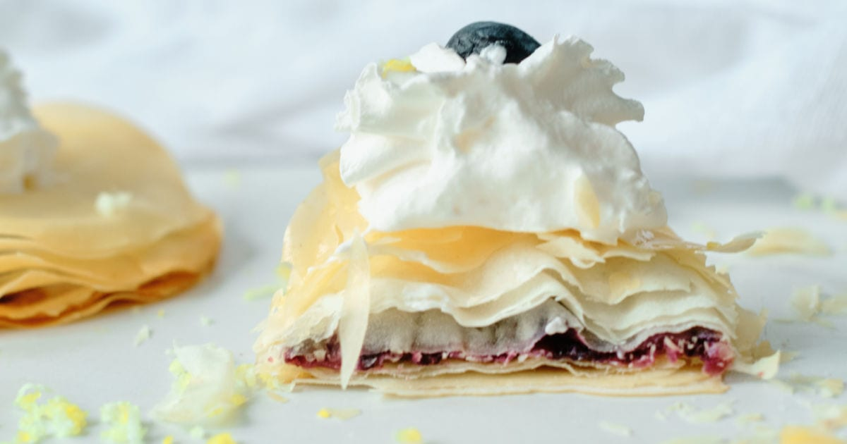 side view of blueberry filo dough pastry topped with whipped cream.