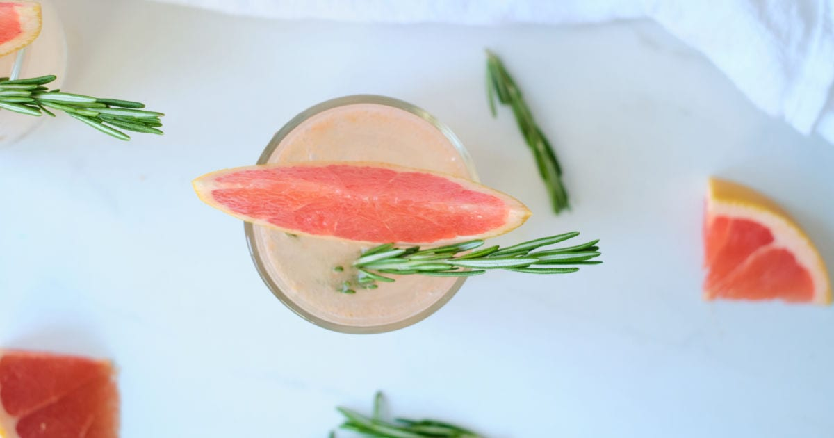 overhead view of sparkling grapefruit juice with rosemary.