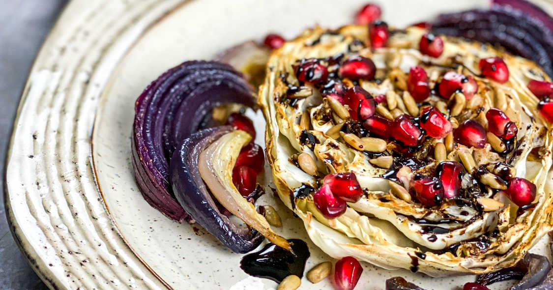 stoneware plate with cabbage steak topped with pomegranate arils and sunflower seeds.