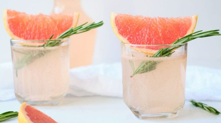 two glasses of sparkling pink grapefruit juice with rosemary.